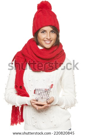 Winter shopping concept. Smiling beautiful woman in winter red hat and scarf holding empty shopping basket over white background - stock photo