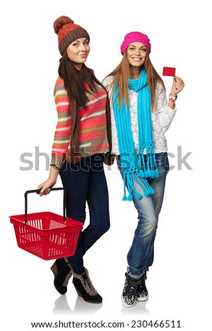Winter shopping concept. Two full length of happy girls in winter hat and scarf showing blank credit card and holding empty shopping basket, on white background - stock photo