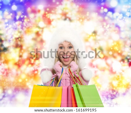 Winter shopping woman happy smiling holding bags over abstract colorful lights background - stock photo