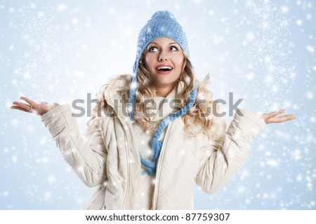 winter shot of a young pretty woman wearing a light blue hat and white sweater and scarf over white, she's looking up with an expression of surprise - stock photo