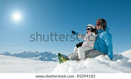 Winter, ski and sun - father and daughter on winter vacation ( copy space) - stock photo