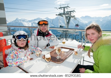 Winter, ski - family enjoying lunch in winter mountains - stock photo