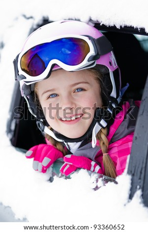 Winter, ski holiday - portrait of lovely skier in the snowy car