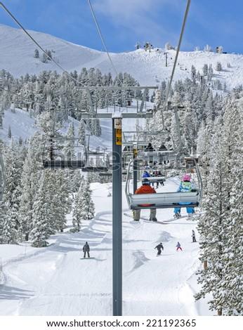 Winter ski lift riders - stock photo
