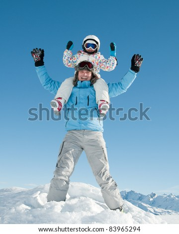 Winter, ski, sun and fun - happy family in winter resort - stock photo