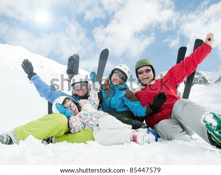 Winter, ski, sun and fun - happy skiers in ski resort - stock photo