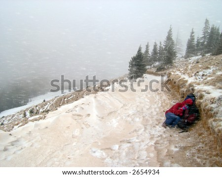 winter snow and dust storm with dismay human  figure on mountainside road and mountain live farming settlement behind - stock photo