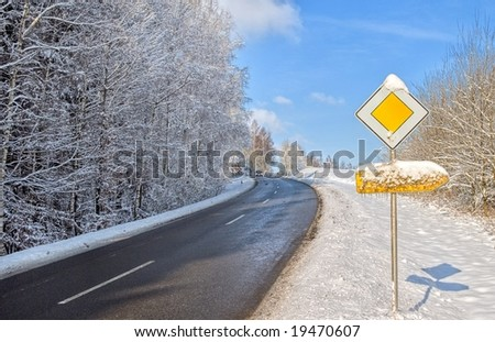 Winter snow-covered asphalt road and traffic sign in Germany, Europe - stock photo