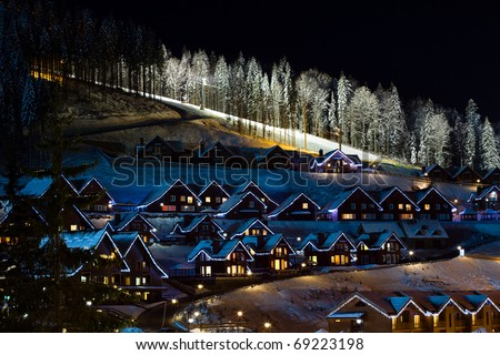 Winter snow covered houses in the mountains. Ski resort in the night