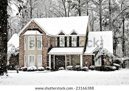 Winter snow falling on an executive home - stock photo