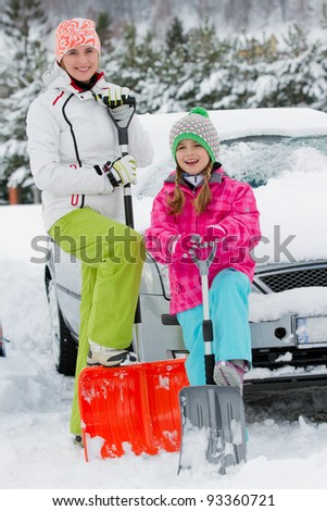 Winter, snow - family is shoveling the road and the car of snow - stock photo