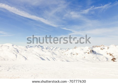 Winter snow mountain landscape with blue cloudy sky. Alps. France.