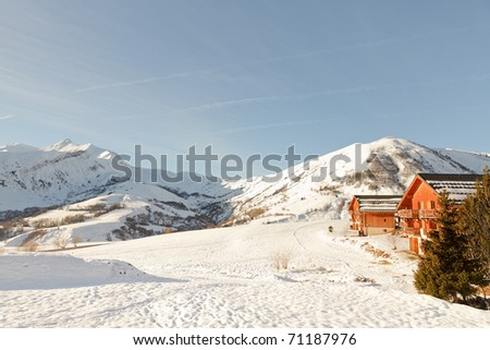 Winter snow mountain landscape with chalets under blue sky. Apartments. Cottages. Wooden houses. Recreational. Alps. France. - stock photo