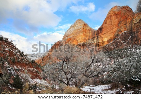 Winter Snow On The Flanks Of Red Rock Peaks Made Golden By Late Afternoon Sunlight At Zion National Park, Utah, USA - stock photo