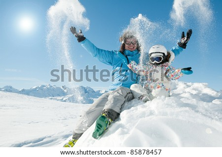 Winter, snow, sun and fun - happy skiers playing in snow - stock photo