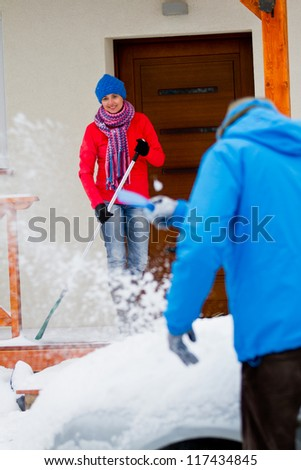 Winter, snow - the family is clearing of snow in front of the house and car