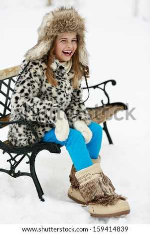 Winter, snow, winter fashion girl - happy young girl playing in winter park - stock photo