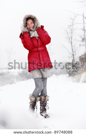 Winter snow woman having fun outside. Cute happy smiling young mixed race Asian Caucasian woman playful in the snow. - stock photo