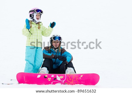 Winter, snowboarding - portrait of young snowboarder girls on ski slope - stock photo