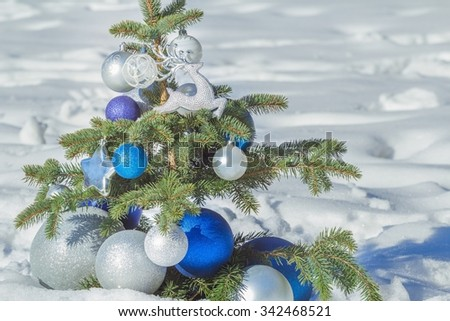 Winter snowy evergreen Christmas tree decorated with shiny ornaments and baubles - stock photo