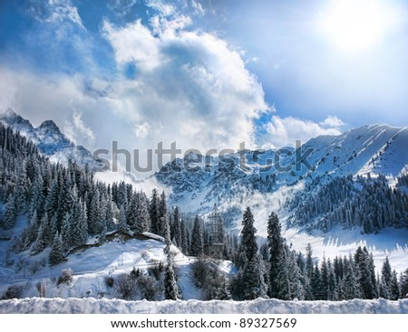 Winter Snowy Mountains valley with fog and sun in Chumbulak, Almaty, Kazakhstan - stock photo