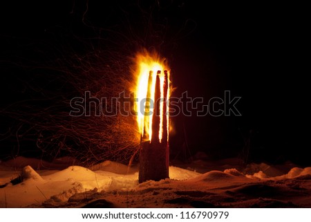Winter solstice pagan traditions in Latvia. Yule log burning ritual. The ritual is symbolic of joint effort to combat the power of darkness and to turn toward the light once again. - stock photo