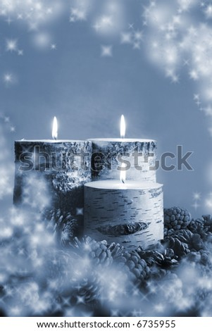 Winter Sparkle:  Three birch candles nestled in some pine cones with a wintry sparkle. - stock photo