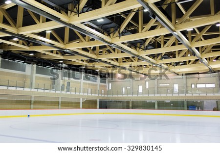 winter, sport, architecture and leisure concept - ice skating rink indoors