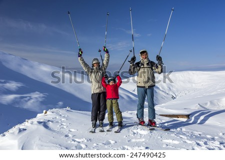 Winter sport family. Family of three people - parents and little daughter - on winter mountains background - stock photo
