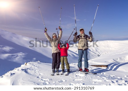 Winter sport family. Family of three people - parents and little daughter - on winter mountains background happy laughing faces victory raised hands with poles - stock photo