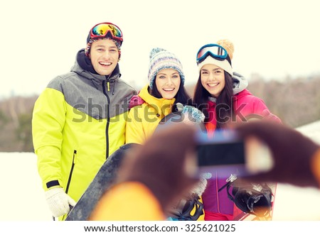 winter sport, leisure, friendship, technology and people concept - happy friends with snowboards and smartphone taking picture