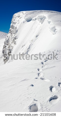 Winter steep crag and human footprint on snow follow to the precipice (Ukraine, Carpathian Mt's, Svydovets Ridge, Blyznycja Mount). Four shots stitch image.