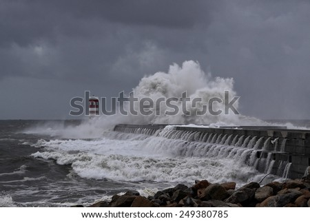 Winter storm with big waves and dark sky at the mouth of the River Douro, Porto, Portugal - stock photo