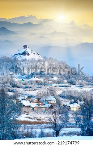 Winter sunrise above the mountain village covered with fresh morning snow - stock photo