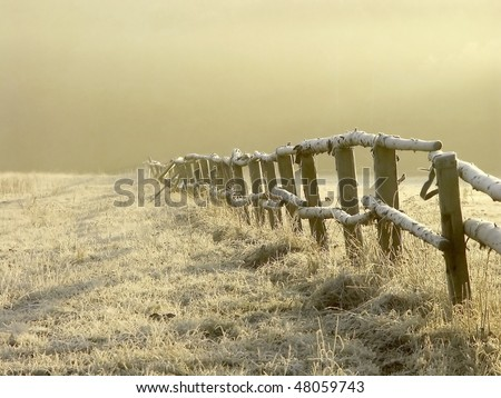 Winter sunrise over misty grassland covered with frost with wooden fence in the foreground. Photo taken in January. - stock photo