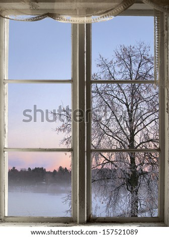 winter sunset and tree with rime frost seen through old window - stock photo