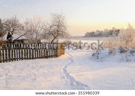 Winter sunset at the village - beautiful rural landscape with field and frosty trees under the snowfall - stock photo