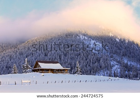 Winter sunset with a log cabin, Utah, USA. - stock photo