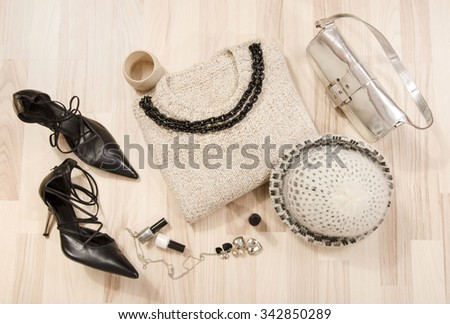 Winter sweater and accessories arranged on the floor. Woman black with silver accessories, high heels, wool hat, necklace and purse. - stock photo