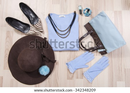 Winter sweater and accessories arranged on the floor. Woman blue and brown accessories, high heels, hat, necklace and gloves lied down. - stock photo