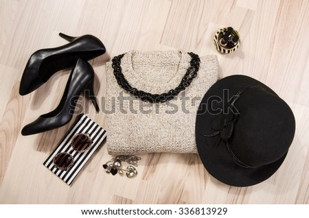 Winter sweater and accessories arranged on the floor. Woman sweater with silver accessories, high heels, black hat, necklace and nail polish. - stock photo
