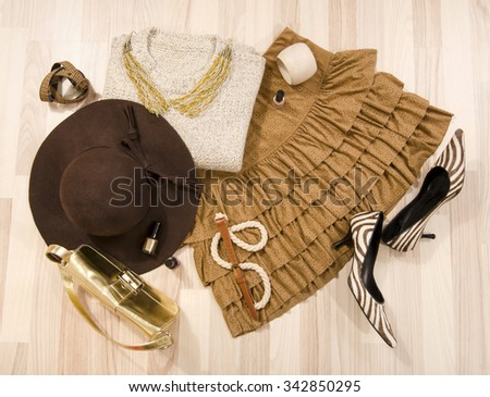 Winter sweater and leather skirt with accessories arranged on the floor. Woman brown outfit with matching hat, necklace, belt and purse lied down. - stock photo