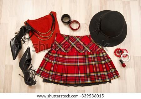 Winter sweater and plaid skirt with accessories arranged on the floor. Woman red outfit with matching hat, necklace, bracelet and nail polish lied down. - stock photo