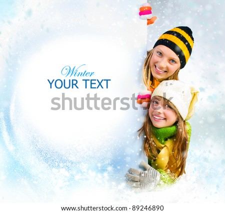 Winter teenage Girls peeking from behind blank sign billboard. Space for Your Text.Sale - stock photo