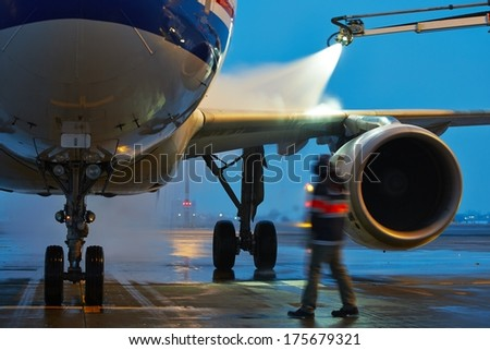 Winter time at the airport. Deicing of the airplane. - stock photo