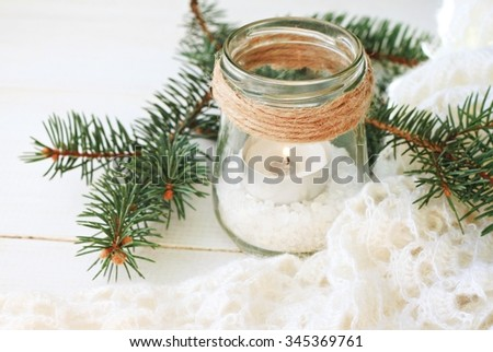 Winter time candle holder for cozy home interior decoration: jar, candle, pine boughs,wool warm plaid. - stock photo