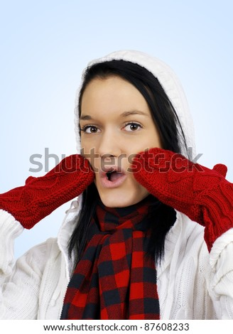 Winter time concept: cute oh my it's cold friendly natural young woman with red mittens and white hoodie over light blue background. - stock photo