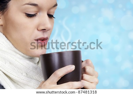 Winter time concept: friendly natural young woman with white wool scarf blowing on her hot chocolate, coffee or tea in a brown mug over light blue fun background. - stock photo