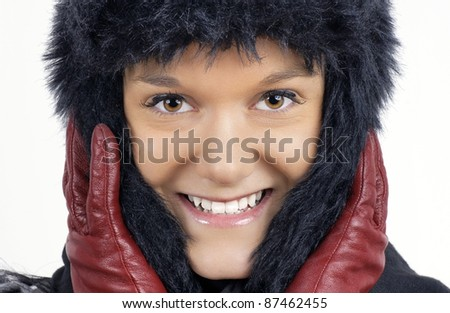 Winter time: portrait of smiling friendly natural young woman wearing black faux fur hat with red leather gloves. - stock photo