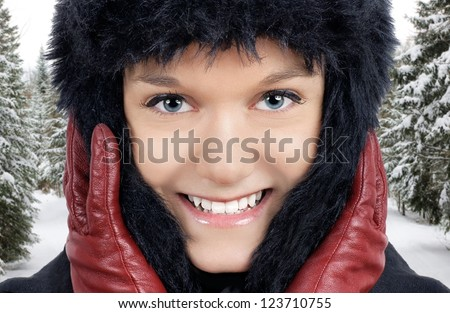 Winter time: portrait of smiling young woman outside in the snowy forest where it is very cold, keeping warm with her black faux fur hat and red leather gloves. - stock photo